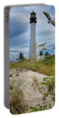 Pelican Flying Over Cape Florida Lighthouse Portable Battery Charger by Justin Kelefas