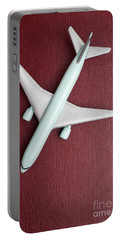 Portable Battery Charger featuring the photograph Toy Airplane Over Red Book Cover by Edward Fielding