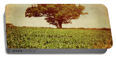 Portable Battery Charger featuring the photograph Tree On Edge Of Field by Lyn Randle