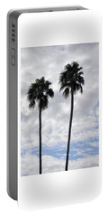 Twin Palm Trees Silhouetted Against Cloudy Blue Sky Portable Battery Charger