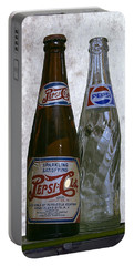 Two Pepsi Bottles On A Table Portable Battery Charger