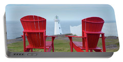 Two Red Adirondack Chairs Looking Out To A Lighthouse Portable Battery Charger by Art Whitton
