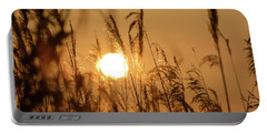 View Of Sun Setting Behind Long Grass B Portable Battery Charger