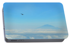 Portable Battery Charger featuring the photograph White-necked Raven With Twig Soaring Over Mount Meru by Jeff at JSJ Photography