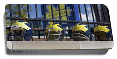 Wolverine Helmets Of Different Eras On Stadium Wall Portable Battery Charger