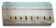 Portable Battery Charger featuring the photograph Wood Pilings In Shallow Waters by Colleen Kammerer