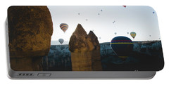 hot air balloons for tourists flying over rock formations at sunrise in the valley of Cappadocia. Portable Battery Charger