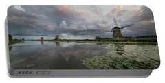 Portable Battery Charger featuring the photograph Dramatic Sky Over Three Windmills In Holland by IPics Photography