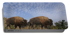 Group Of Bison Walking Against Rocky Mountains  Portable Battery Charger