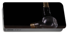 Portable Battery Charger featuring the photograph Two Light Bulbs Arranged On A Wooden Table  by Vincent Billotto