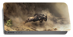 Wildebeest Leaps From The Bank Of The Mara River Portable Battery Charger