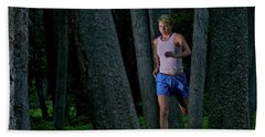 A Woman Trail Running In The Forests Beach Towel