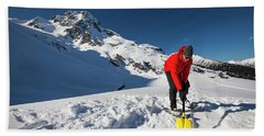A Climber Shovels Snow In Order To Make Beach Towel