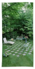 A Garden With Checkered Pavement Beach Towel