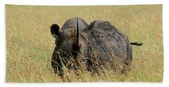 A Rhino Standing In The Grass Beach Towel