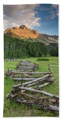 A Scenic Field With Fence And Mountains Beach Towel