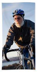 A Senior Man Bikes In Homer, Alaska Beach Towel