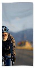 A Senior Man Road Bikes With Mountains Beach Towel