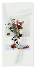 A Studio Shot Of A Vase Of Flowers And A Garden Beach Towel
