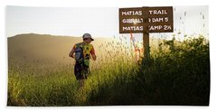 A Trail Runner Passes A Sign And Trail Beach Towel