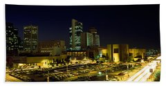 Buildings In A City Lit Up At Night Beach Towel by Panoramic Images