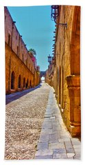 Rhodes Cobbled Street Beach Towel by Scott Carruthers