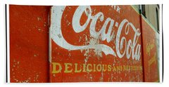 Coca-cola On The Army Store Wall Beach Towel by Kathy Barney