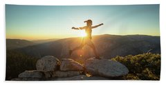 Person Leaping Along Rocks At Sunset Beach Towel