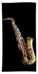 Single Saxophone Against Black Beach Towel