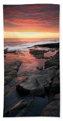 Sunset Over Rocky Coastline Beach Towel