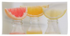 Three Fruit Juices In Bottles With Wedges Of Fresh Fruit Beach Towel