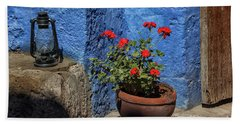 Beach Towel featuring the photograph Red Geranium Near A Blue Wall by Patricia Hofmeester