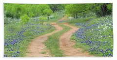 A Dirt Road Lined By Blue Bonnets Of Texas Beach Towel