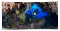 A Diver Peers Through A Coral Encrusted Beach Towel