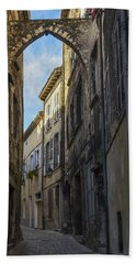 Beach Towel featuring the photograph A Narrow Street In Viviers by Allen Sheffield