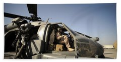 A Pilot Sits In The Cockpit Of A Hh-60g Beach Towel