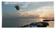 Bald Eagle Flying Over A Jetty At Sunset Beach Towel