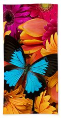 Blue Butterfly On Brightly Colored Flowers Beach Towel by Garry Gay