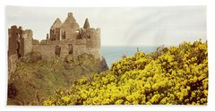 Beach Towel featuring the photograph Castle Ruins And Yellow Wildflowers Along The Irish Coast by Juli Scalzi
