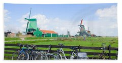 dutch windmills with bikes in Zaanse Schans Beach Towel
