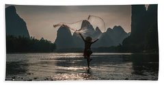 Fisherman Casting A Net. Beach Towel