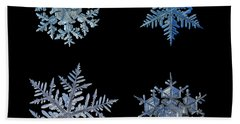 Four Snowflakes On Black Background Beach Towel