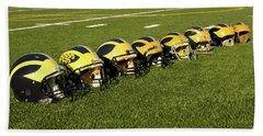 Helmets Of Different Eras On The Field Beach Sheet