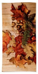Beach Towel featuring the photograph Leaves And Nuts And Red Ornament by Rebecca Cozart