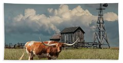 Longhorn Steer In A Prairie Pasture By Windmill And Old Gray Wooden Barn Beach Towel