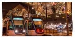 Night View Of Two Trams At Glories Station  Beach Towel
