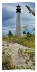 Pelican Flying Over Cape Florida Lighthouse Beach Towel by Justin Kelefas