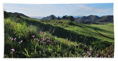Beach Towel featuring the photograph Purple Flowers And Green Hills Landscape by Matt Harang