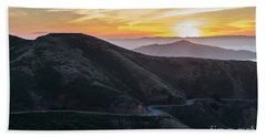 Road On The Edge Of The Mountain With Sunrise In The Background Beach Towel