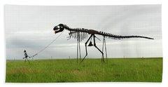 Skeletal Man Walking His Dinosaur Statue Beach Towel